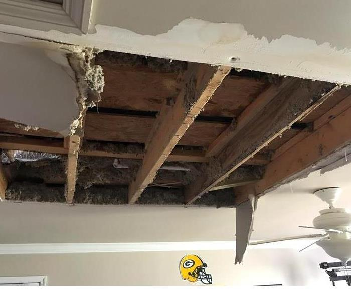 This is a photo of a damaged ceiling from a damaged roof.